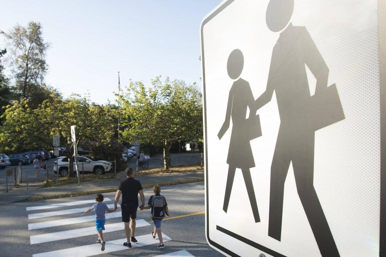 Children walk with their parents to Sherwood Park Elementary in North Vancouver for the first day back to school on Sept. 10, 2020. THE CANADIAN PRESS/Jonathan Hayward