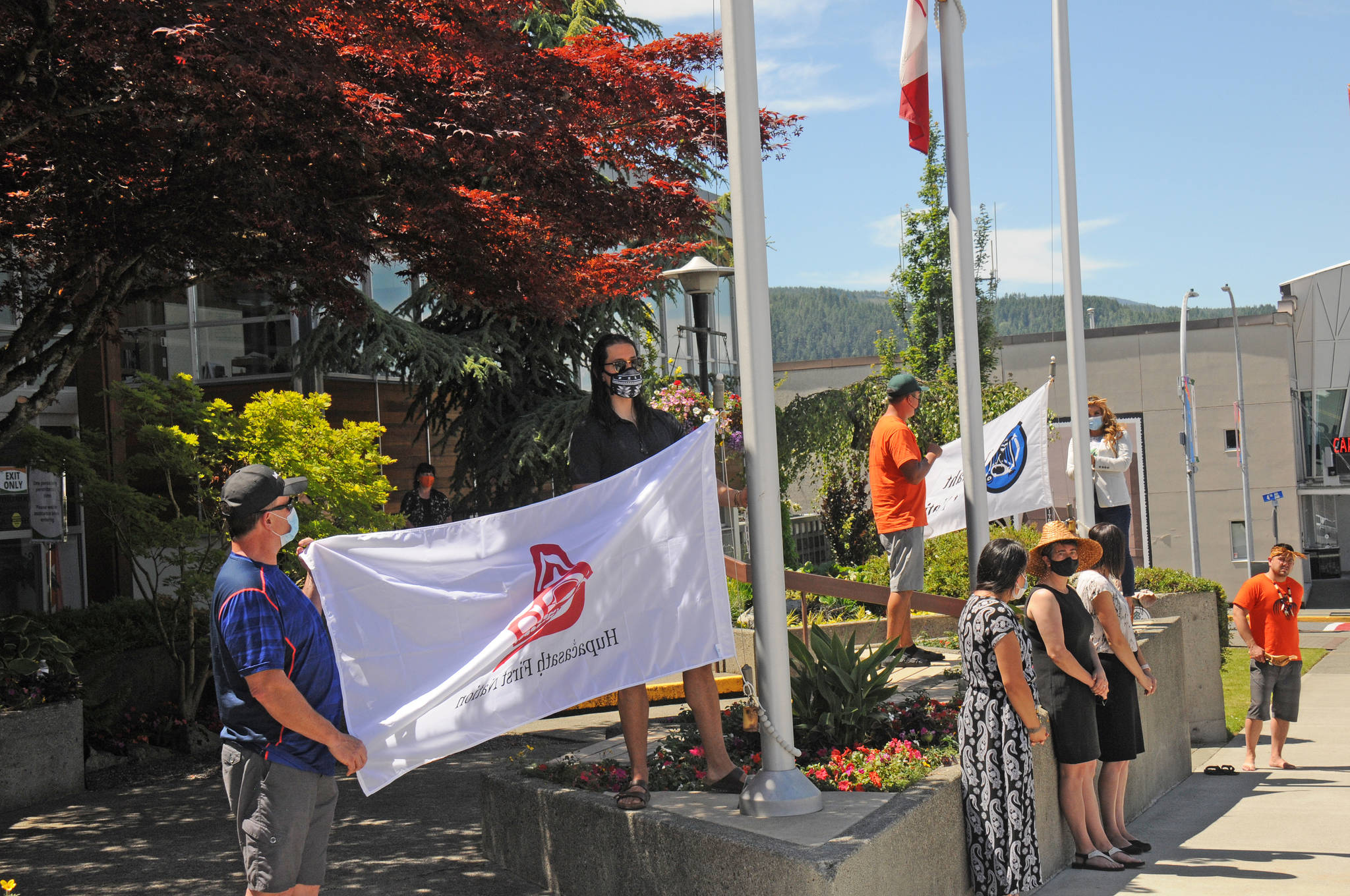 Council members and witnesses from the Hupacasath First Nation, left, and Tseshaht First Nation, right, prepare to raise their respective flags in front of Port Alberni City Hall on Monday, June 21, 2021. The flags will permanently fly as part of the city's reconciliation work. (SUSAN QUINN/ Alberni Valley News)