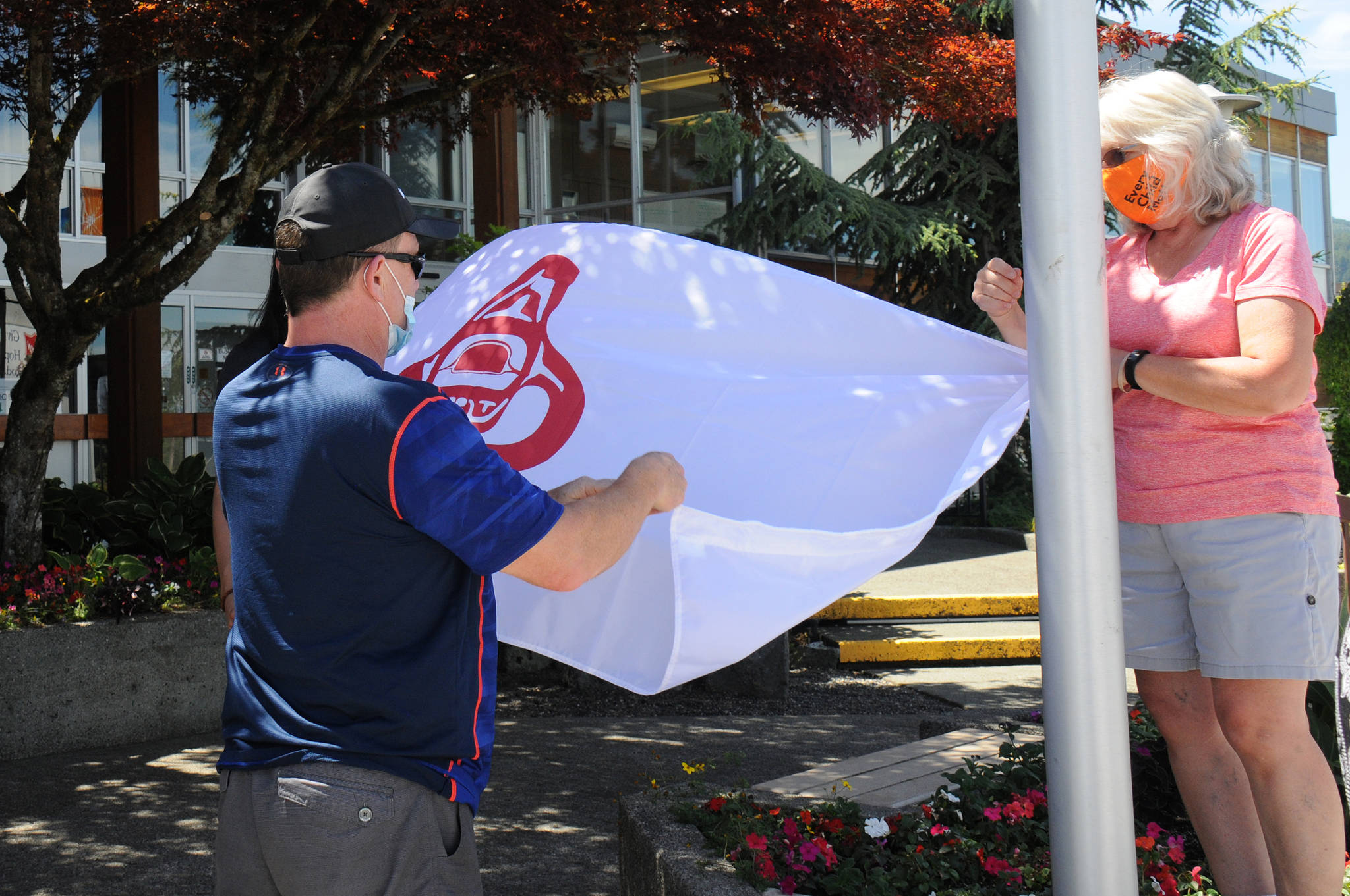 A City of Port Alberni employee assists a member of Hupacasath First Nation in preparing the nation's flag to be raised in front of Port Alberni City Hall on Monday, June 21, 2021. (SUSAN QUINN/ Alberni Valley News)