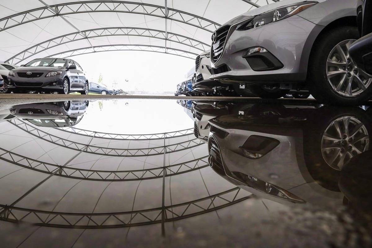 Vehicles for sale are seen under a protective tent at a Mazda dealership in Calgary, Thursday, July 14, 2016. THE CANADIAN PRESS/Jeff McIntosh
