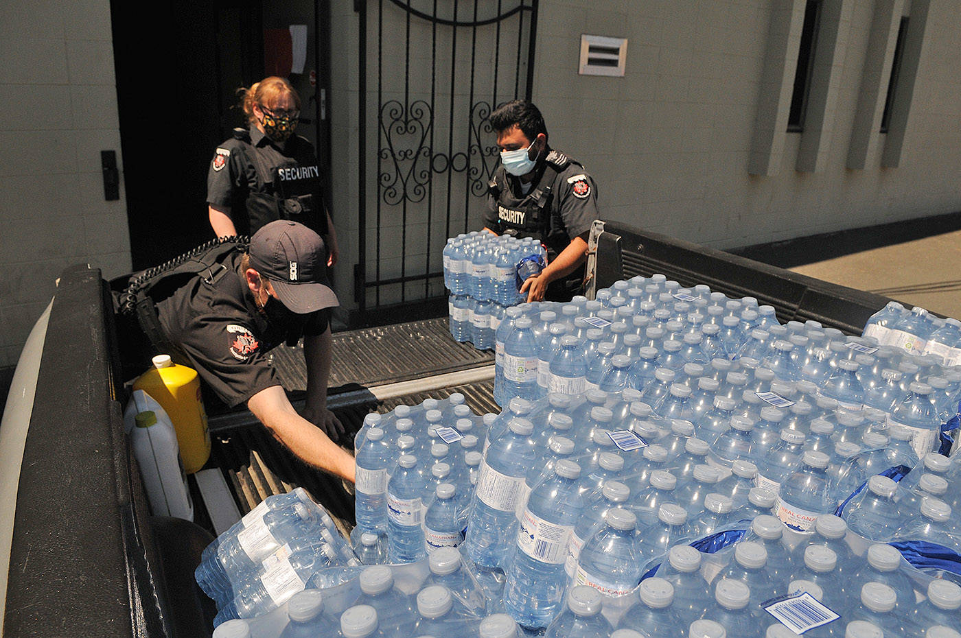 Griffin Security staff unload donations of bottled water that will be handed out to Chilliwack's homeless community and others. They are seen here on Tuesday, June 22, 2021. (Jenna Hauck/ Chilliwack Progress)