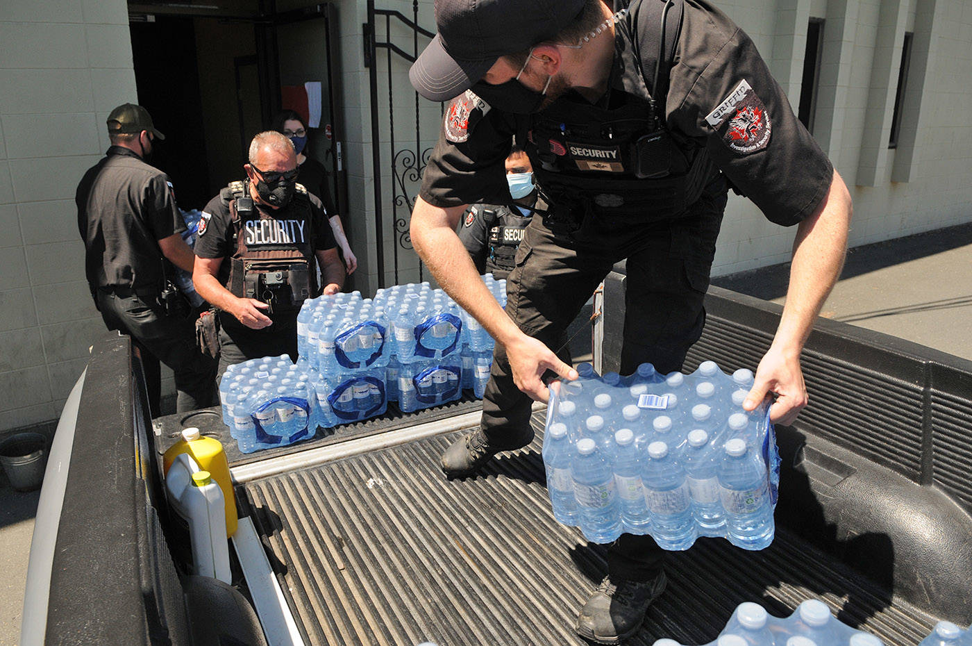 Cody Mendel (foreground) and fellow Griffin Security staff unload donations of bottled water that will be handed out to Chilliwack's homeless community and others. They are seen here on Tuesday, June 22, 2021. (Jenna Hauck/ Chilliwack Progress)