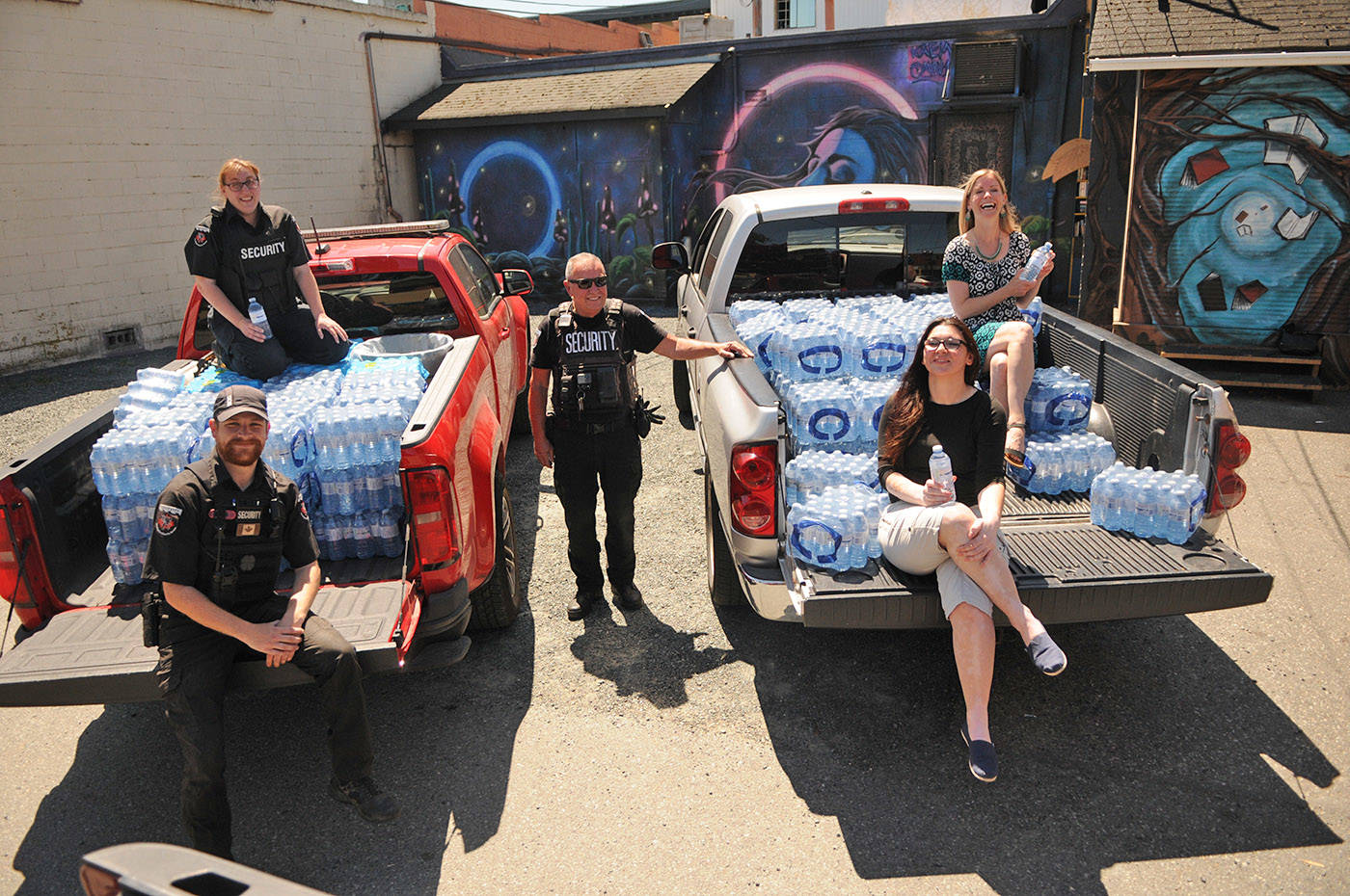From left, Cody Mendel, Sabrina Peterson and Brian Goldstone (all from Griffin Security) along with Trisha Mercer and Amber Price were all part of collecting donations of bottled water that will be handed out to Chilliwack's homeless community and others. They are seen here on Tuesday, June 22, 2021. (Jenna Hauck/ Chilliwack Progress)