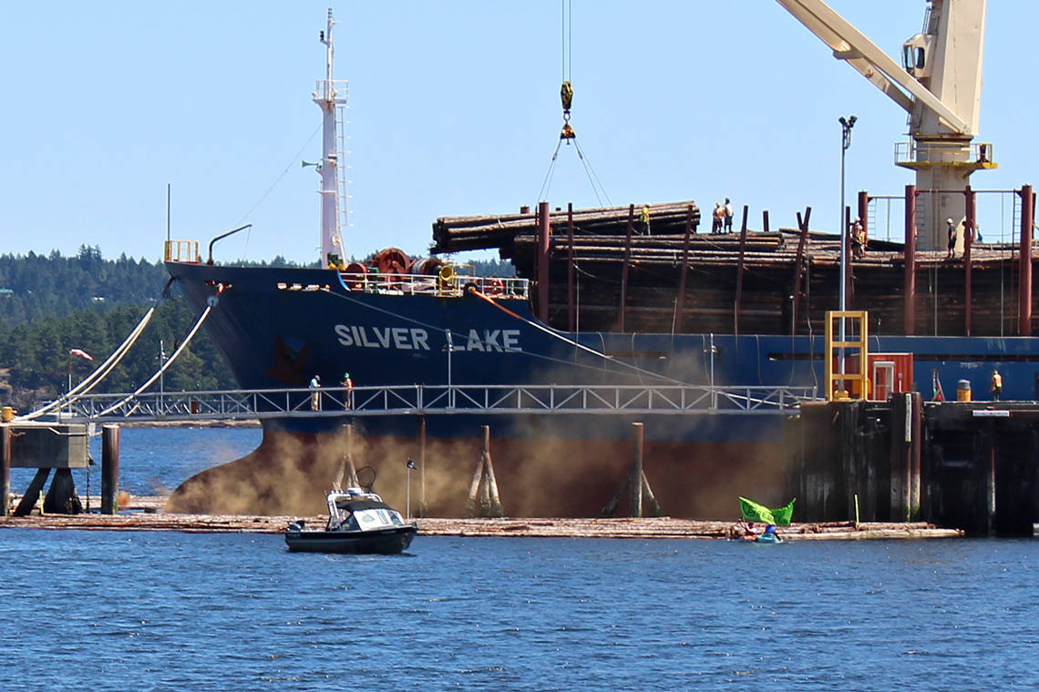 Extinction Rebellion Nanaimo sets off a smoke bomb in front of a log carrier ship Tuesday, June 22, in Nanaimo harbour. (Greg Sakaki/News Bulletin)