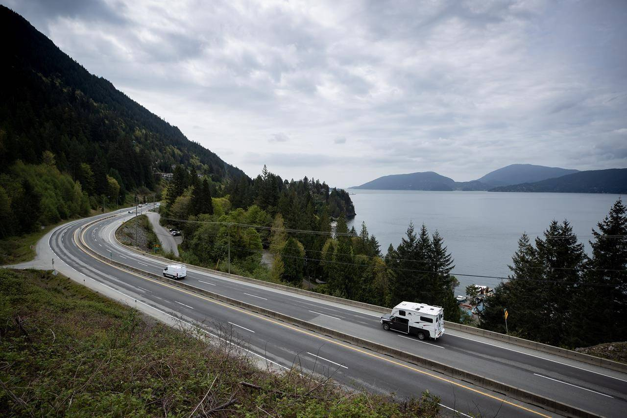 A motorist with a truck camper travels on the Sea-to-Sky highway between Horseshoe Bay and Lions Bay, B.C., on Friday, April 23, 2021. A new report from Canada's parliamentary budget officer says the speed at which change needs to happen for how people drive and heat buildings will make it tough for the Liberal government to achieve its latest climate goal. THE CANADIAN PRESS/Darryl Dyck