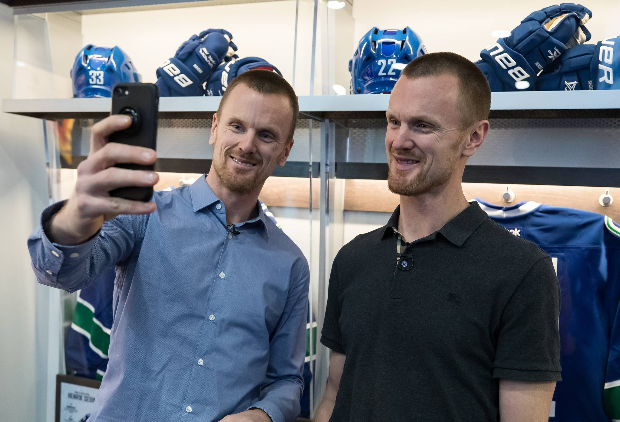 Former Vancouver Canucks' Daniel Sedin, left, and his twin brother Henrik Sedin, both of Sweden, take a selfie together after a media availability ahead of a Wednesday ceremony where the NHL hockey team is scheduled to retire their numbers, in Vancouver, on Monday February 10, 2020. THE CANADIAN PRESS/Darryl Dyck