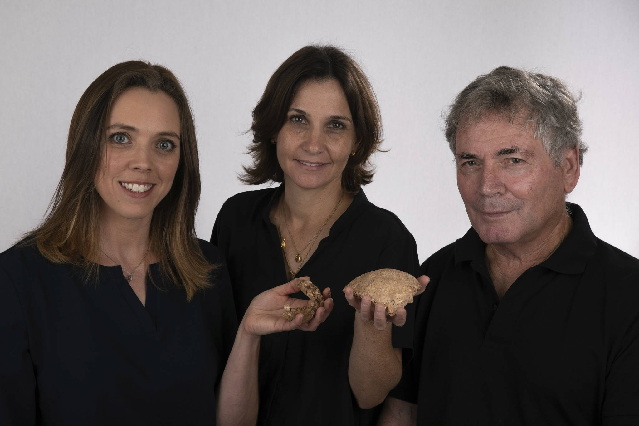 This undated photo provided by Tel Aviv University in June 2021 shows, from left, Rachel Sarig, Hila May and Israel Hershkovitz holding human ancestor fossils found in Neher Ramla, Israel. On Thursday, June 24, 2021, scientists reported that bones found in an Israeli quarry are from a branch of the human evolutionary tree and are 120,000 to 140,000 years old. (Avi Levin and Ilan Theiler/Sackler Faculty of Medicine, Tel Aviv University via AP)