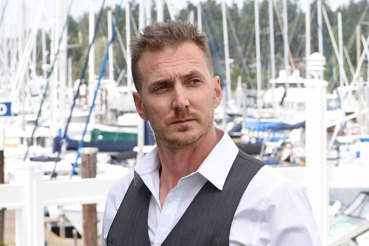 May 15, 2021, 2021 - Kyle Velikovsky photographed in front of boats and boat houses at Van Isle Marina for Secrets and Lives in Boulevard Victoria. Don Denton photograph