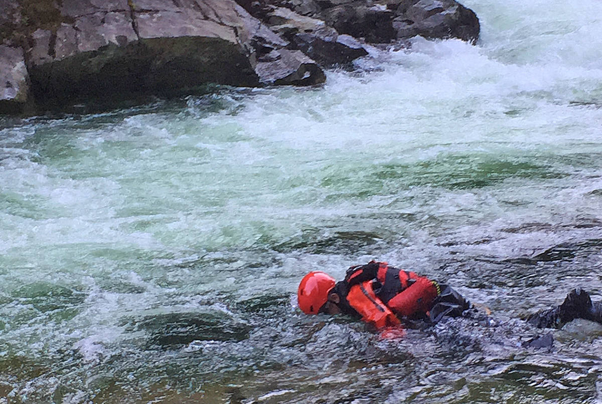 A search and rescue crew member searches in the water. (Special to The News)