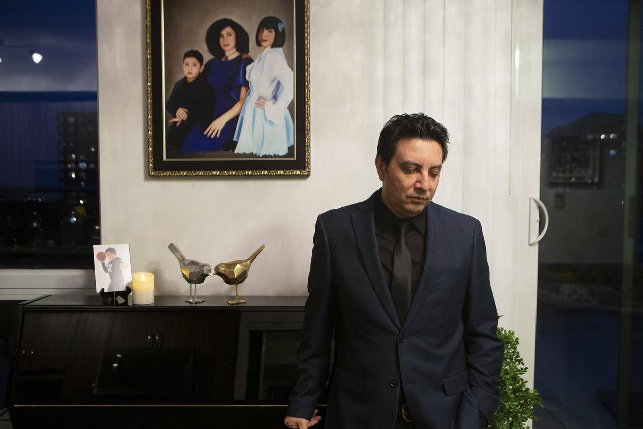 Alireza Ghandchi is photographed in front of a portrait of his wife Faezeh, daughter Dorsa and son Daniel in Richmond Hill , Ont., Friday, January 1, 2021. Ghandchi lost his family after Iranian forces shot down a Ukrainian passenger jet on Jan. 8, 2020. THE CANADIAN PRESS/Chris Young