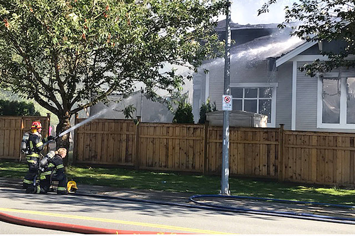 Multiple fire crews attended a house fire in the 21700-block of 50th Avenue in Langley late Friday afternoon. Two homes suffered extensive damage. (Matthew Claxton/Langley Advance Times)