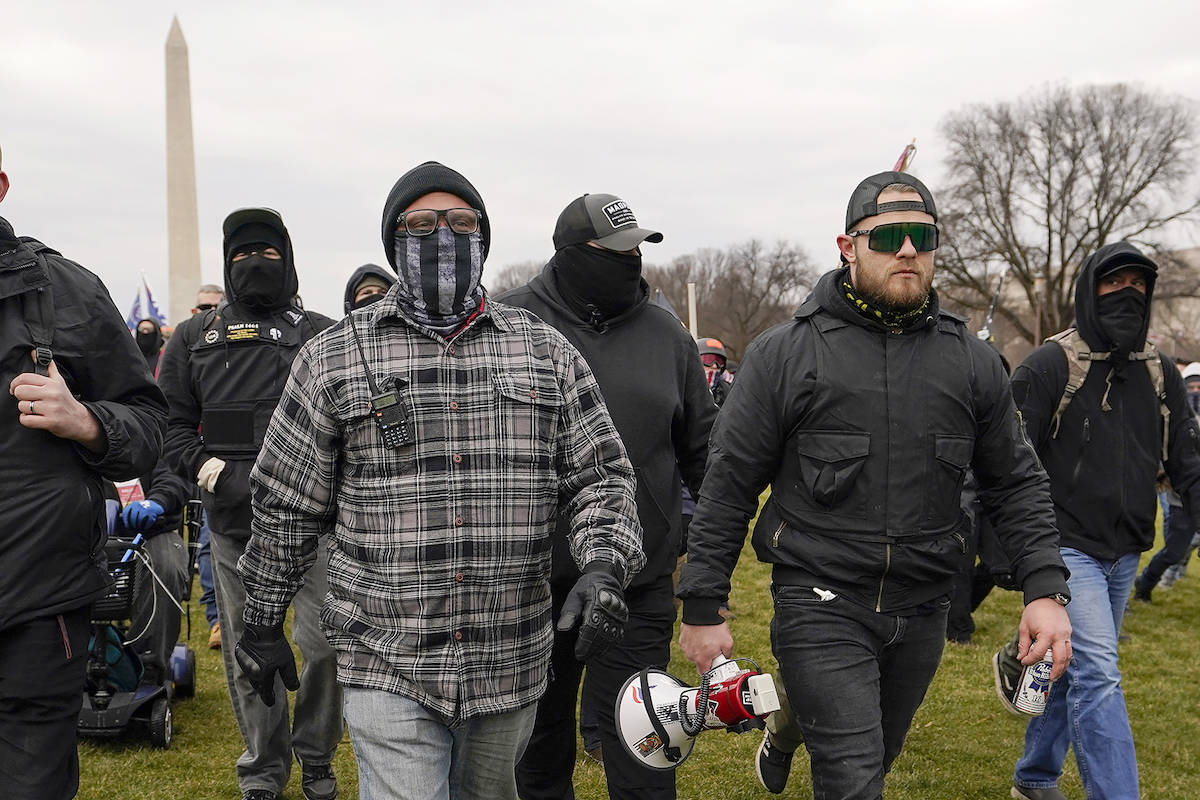 In this Jan. 6, 2021, photo, Proud Boy members Joseph Biggs, left, and Ethan Nordean, right with megaphone, walk toward the U.S. Capitol in Washington, in support of President Donald Trump. (AP Photo/Carolyn Kaster)