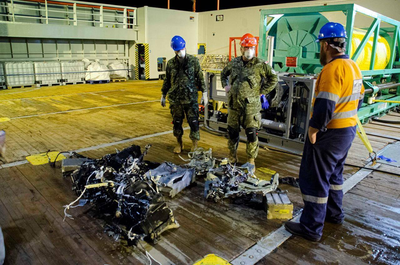Canadian Forces members and EDT Hercules personnel inspect recovered parts of the helicopter Stalker 22 during recovery operations for the aircraft in the Mediterranean Sea on May 31, 2020. THE CANADIAN PRESS/HO-Department of National Defence, Cdr Robert Watt