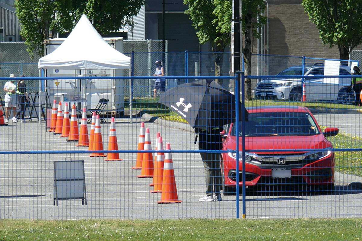 A Fraser Health staffer used a parasol for shade while directing traffic at the testing an immunization centre at Kwantlen Polytechnic University in Langley on Saturday, June 27. On Sunday, the FHA announced the outdoor facility would be shutting down at noon during the heat wave, with people redirected to the indoor facility at Langley Events Centre. (Dan Ferguson/Langley Advance Times)