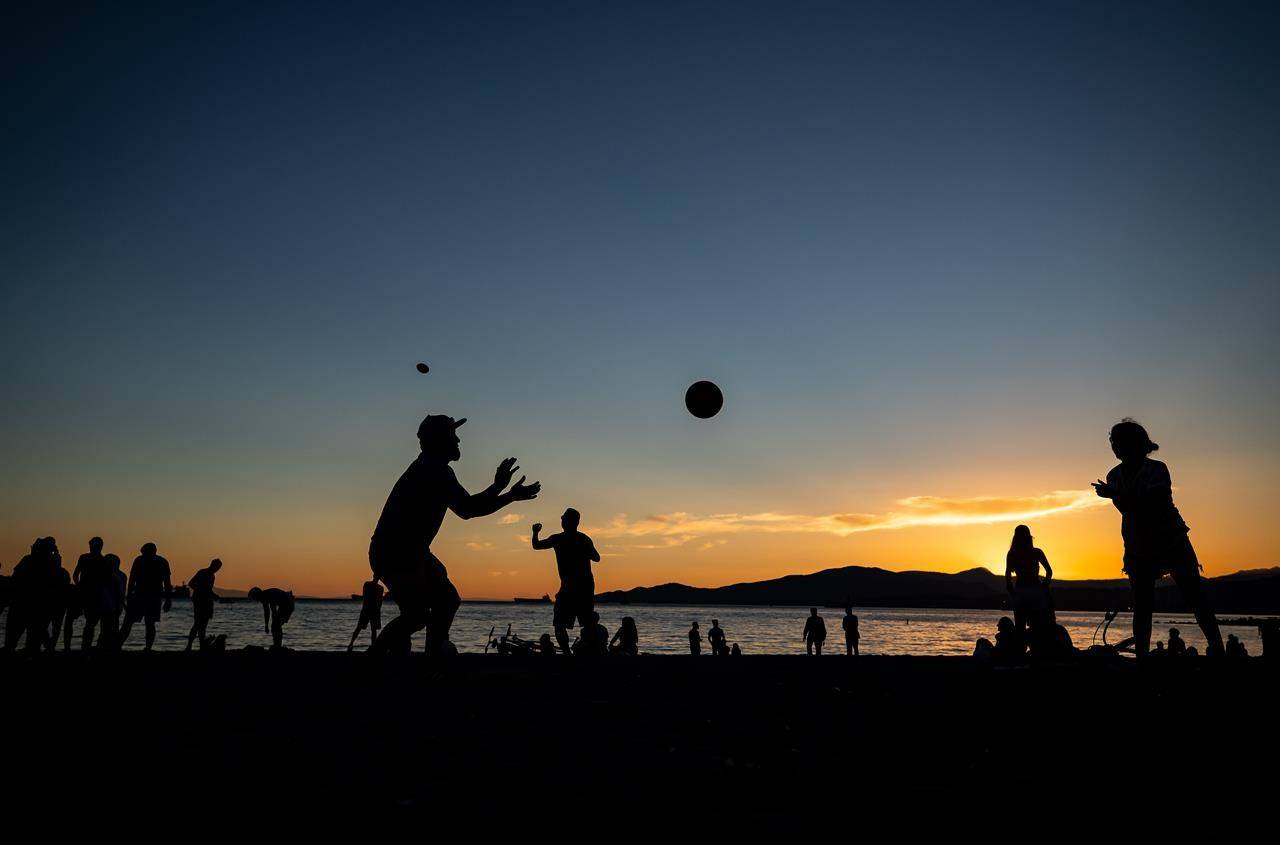 People are silhouetted while playing and gathering at English Bay Beach at sunset, in Vancouver, B.C., on Monday, June 21, 2021. An air quality advisory is in effect for the eastern parts Metro Vancouver and the central Fraser Valley amid a wave of extremely hot and sunny weather. THE CANADIAN PRESS/Darryl Dyck