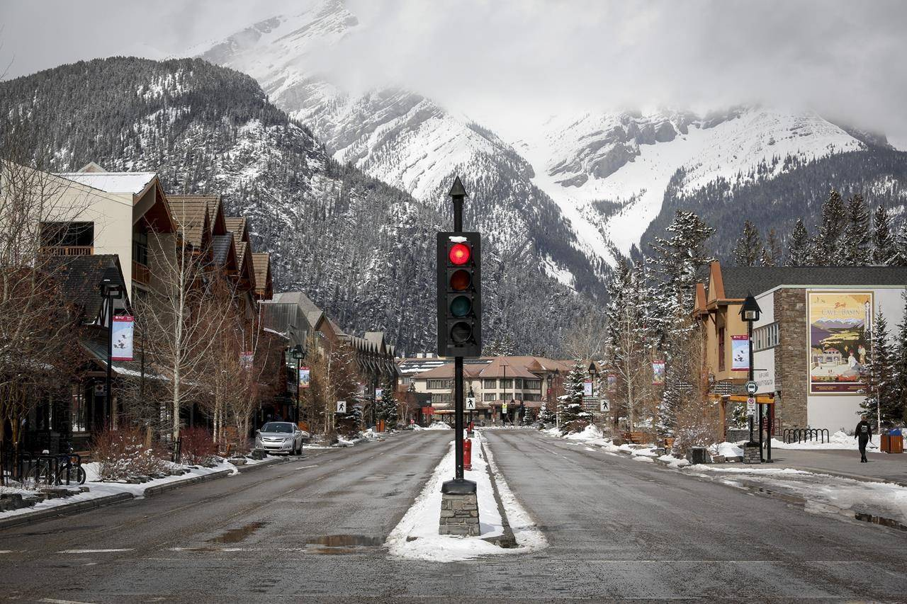 The empty streets of Banff are seen as Parks Canada is restricting vehicles in the national parks and national historic sites due to the COVID-19 pandemic, in Banff, Alta., Tuesday, March 24, 2020. Even as Alberta plans to drop nearly all COVID-19 restrictions on July 1st, local businesses and the Banff National Park's tourism board say they'll be sorely missing international tourists for a second peak summer season in a row. THE CANADIAN PRESS/Jeff McIntosh