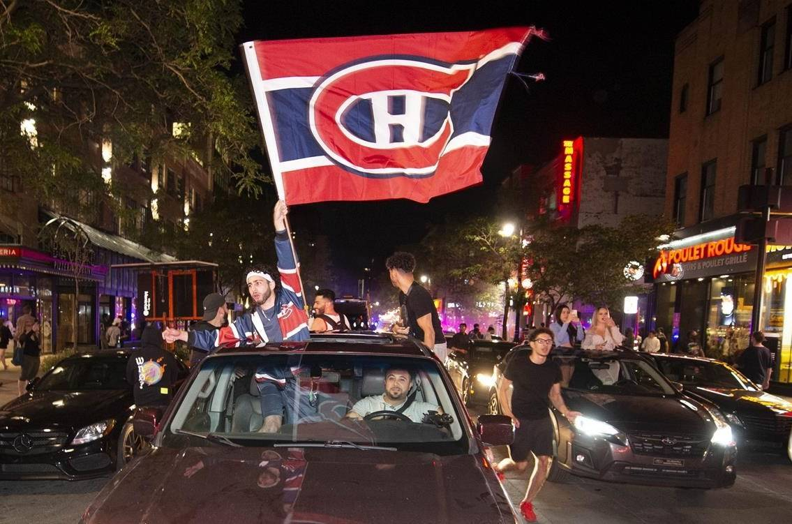 Montreal Canadiens fans celebrate on Rue St Catherine after the Montreal Canadiens defeated the Vegas Golden Knights in overtime game 6 NHL Stanley Cup playoff hockey semifinal action in Montreal, Thursday, June 24, 2021. THE CANADIAN PRESS/Peter McCabe