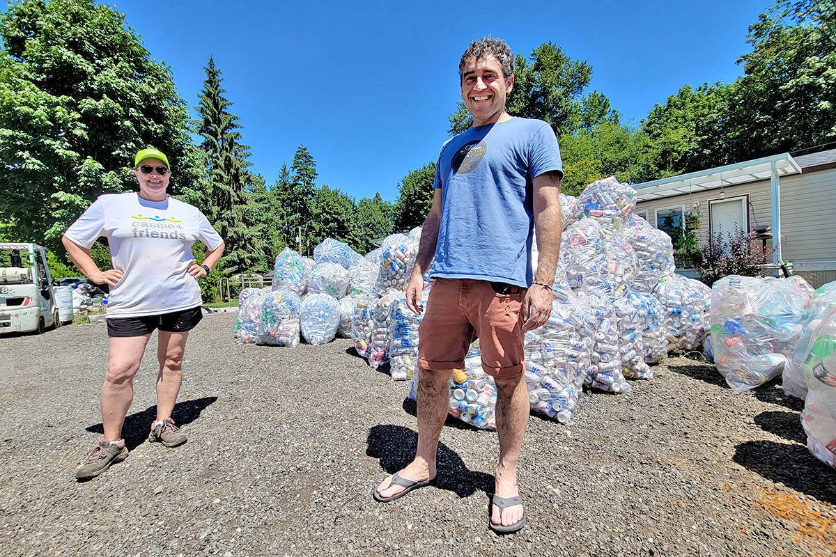 Langley's Charlene Prime and David Porte, founder of the Cassie and Friends charity, pose in front a growing pile of sorted cans at the Prime family's annual bottle drive on Saturday, June 26, to raise funds to fight juvenile arthritis. (Dan Ferguson/Langley Advance Times)