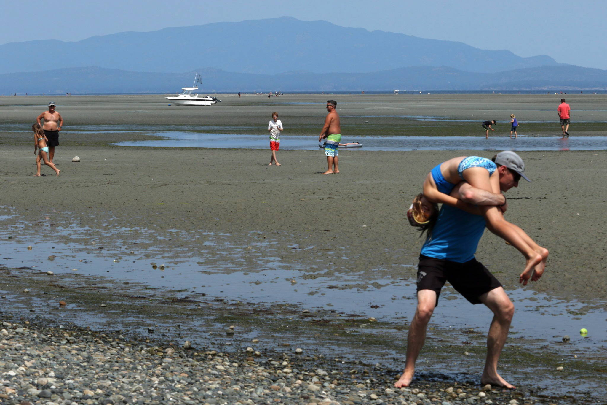 People enjoy the heat wave across Vancouver Island during a low tide at Rathtrevor Beach Provincial Park in Parksville, B.C., on Friday, July 27, 2018. THE CANADIAN PRESS/Chad Hipolito