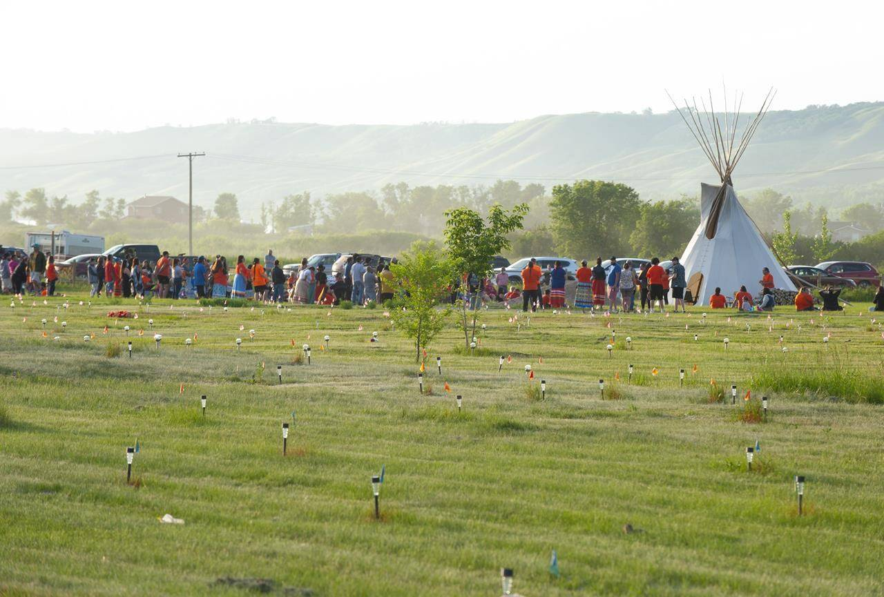 Flags and lights are seen as a vigil takes place where ground-penetrating radar recorded hits of what are believed to be 751 unmarked graves near the grounds of the former Marieval Indian Residential School on the Cowessess First Nation, Sask. on Saturday, June 26, 2021. The board of trustees of Edmonton Catholic Schools has voted unanimously to rename an elementary school bearing the name of a bishop who helped set up residential schools. THE CANADIAN PRESS/Mark Taylor