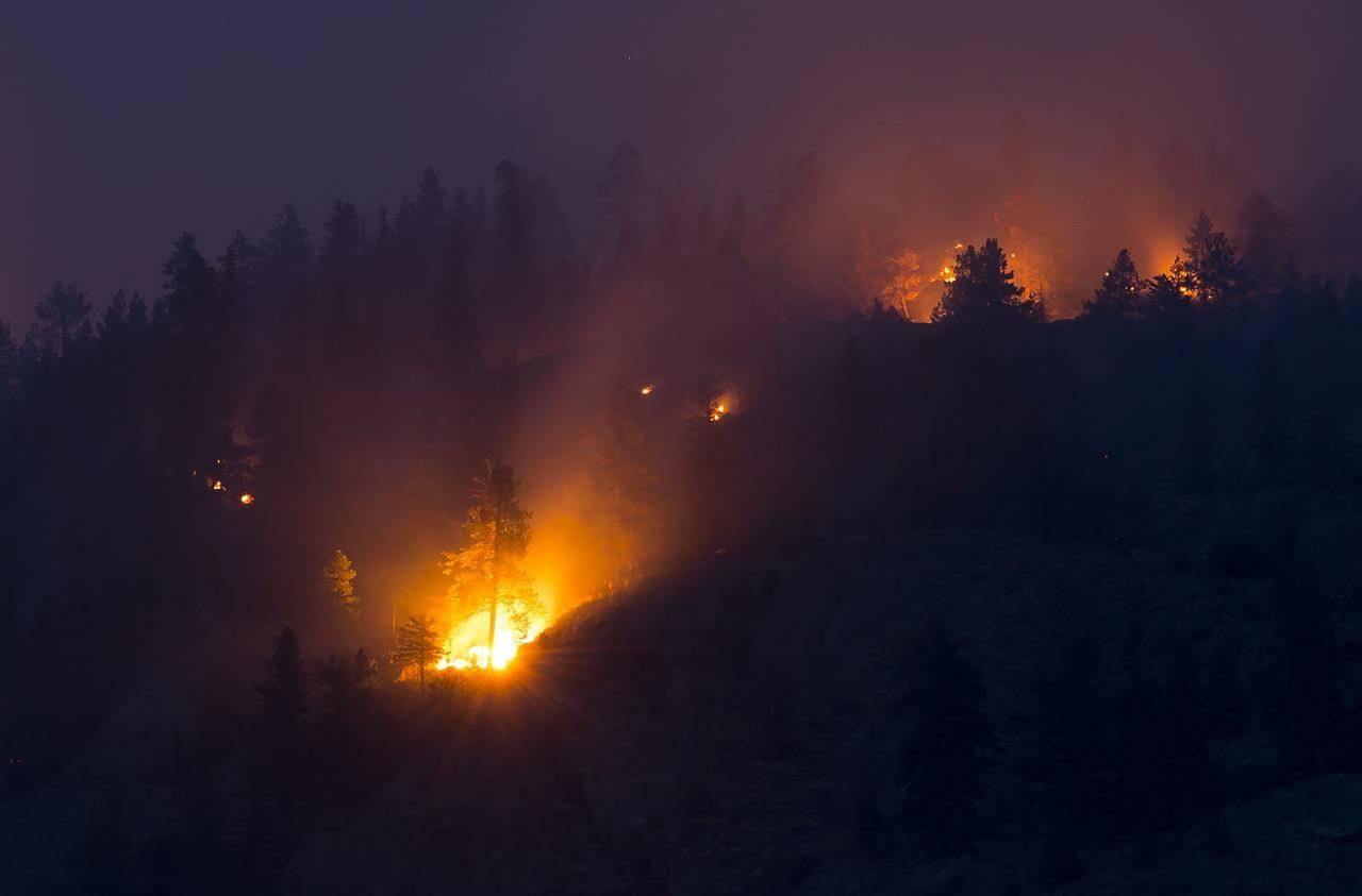 Flare-ups are seen from the Christie Mountain wildfire along Skaha Lake in Penticton, B.C. Thursday, Aug. 20, 2020.THE CANADIAN PRESS/Jonathan Hayward