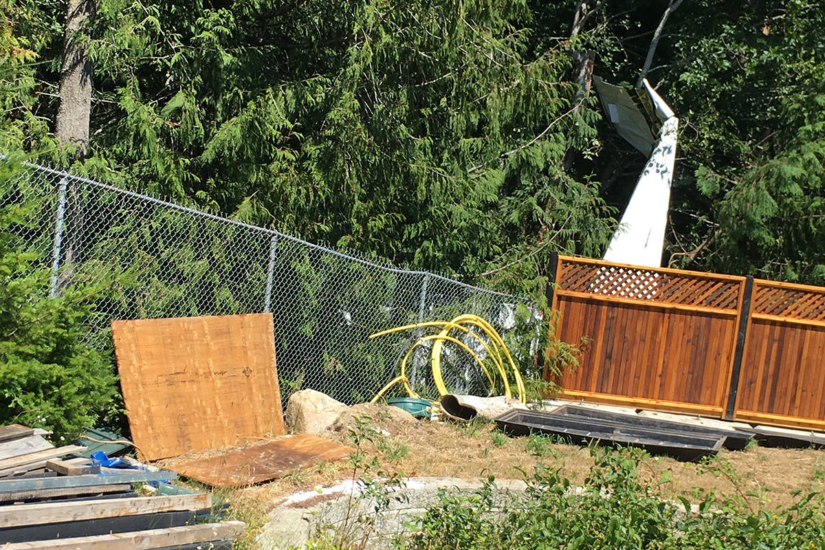 The wing of a small plane can be seen sticking up from a wooded area behind homes in the Haydon Place neighbourhood of Mill Bay. The plane crashed Monday afternoon, June 28, 2021. (Jack Wilke photo)
