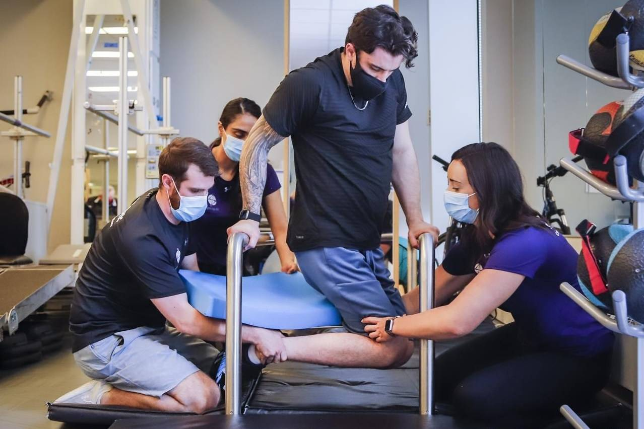 Humboldt Broncos bus crash survivor Ryan Straschnitzki, centre, is helped to turn his body by Eric Daigle, left, and Jill Mack while he attends a physiotherapy session in Calgary on Thursday, June 24, 2021. THE CANADIAN PRESS/Jeff McIntosh