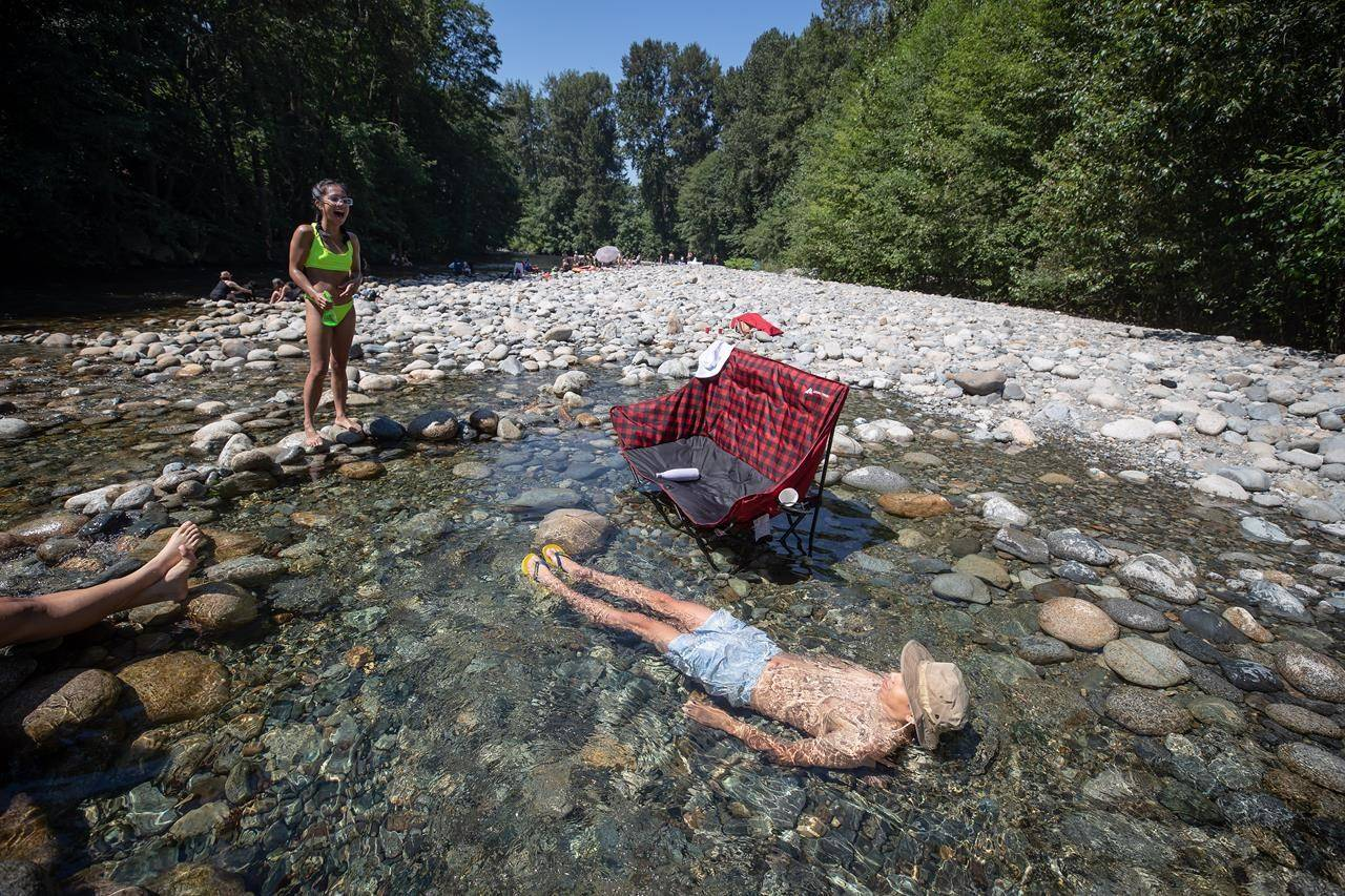 Albert Huynh cools off in the frigid Lynn Creek water as Leanne Opuyes, left, laughs in North Vancouver, B.C., on Monday, June 28, 2021. A stifling heat wave throughout much of Western Canada is unusual because of the nighttime temperatures it is bringing, says an expert. THE CANADIAN PRESS/Darryl Dyck