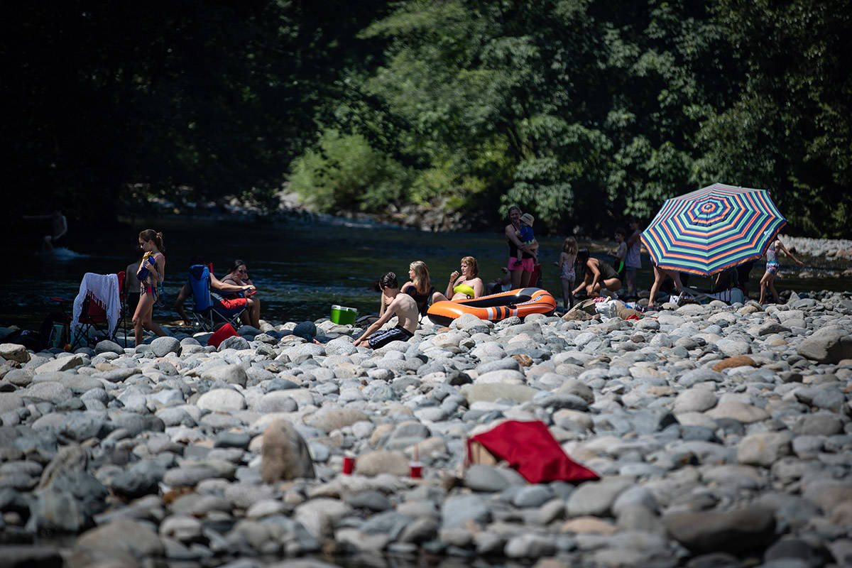 People sit on rocks while cooling off in the frigid Lynn Creek water in North Vancouver, B.C., on Monday, June 28, 2021. Environment Canada warns the torrid heat wave that has settled over much of Western Canada won't lift for days, although parts of British Columbia and Yukon could see some relief sooner. THE CANADIAN PRESS/Darryl Dyck