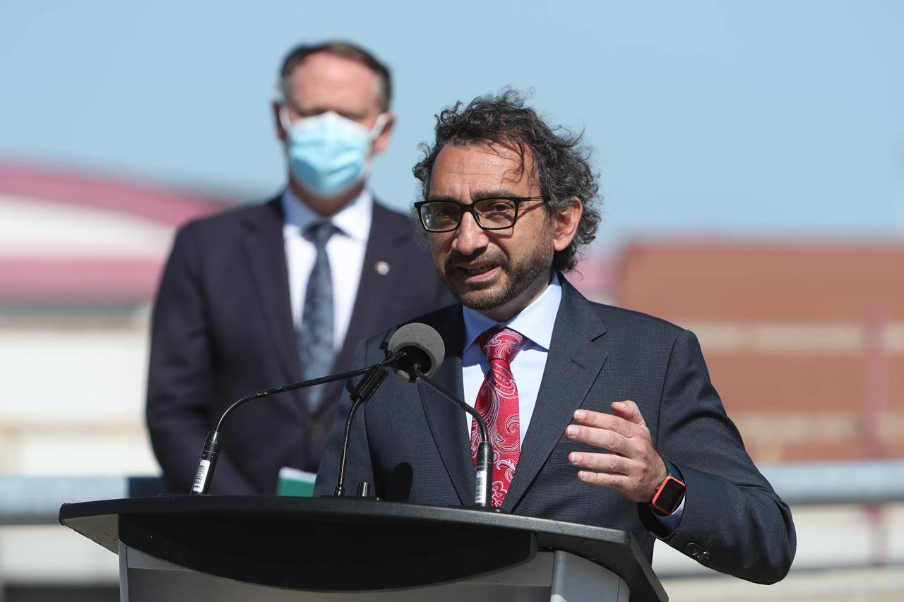 Transport Minister Omar Alghabra speaks while Ottawa South MP David McGuinty looks on during a press conference at the Ottawa MacDonald-Cartier International Airport on Wednesday, June 16, 2021. The Liberal government is speeding up its goal for when it wants to see all light-duty vehicles sold in Canada to be electric.THE CANADIAN PRESS/David Kawai