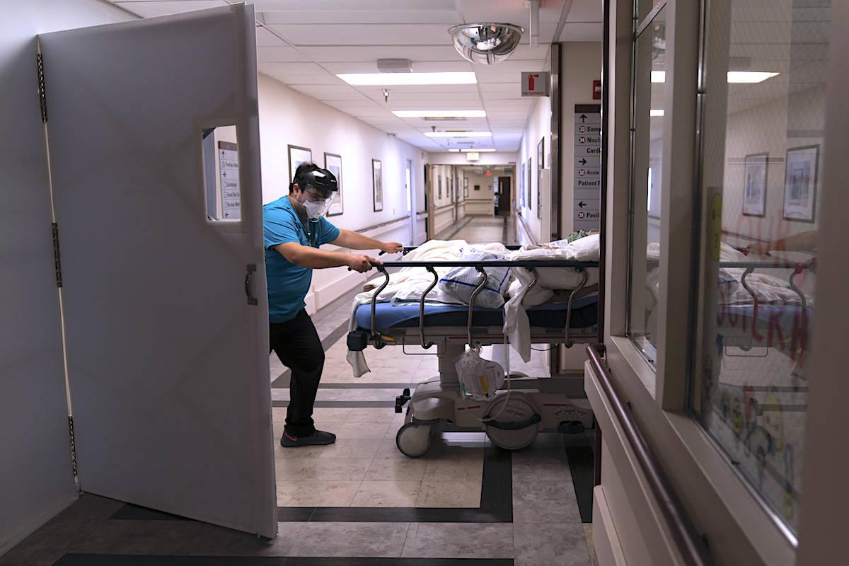 Medical transporter Adrian Parrilla moves a patient into a COVID-19 unit. (AP/Jae C. Hong)
