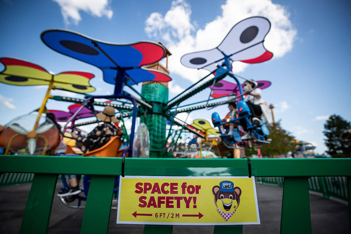 FILE – A sign reminding guests to stay 2 metres apart is seen on a fence as people ride an attraction at Playland amusement park at the Pacific National Exhibition, in Vancouver, on Friday, July 10, 2020. THE CANADIAN PRESS/Darryl Dyck
