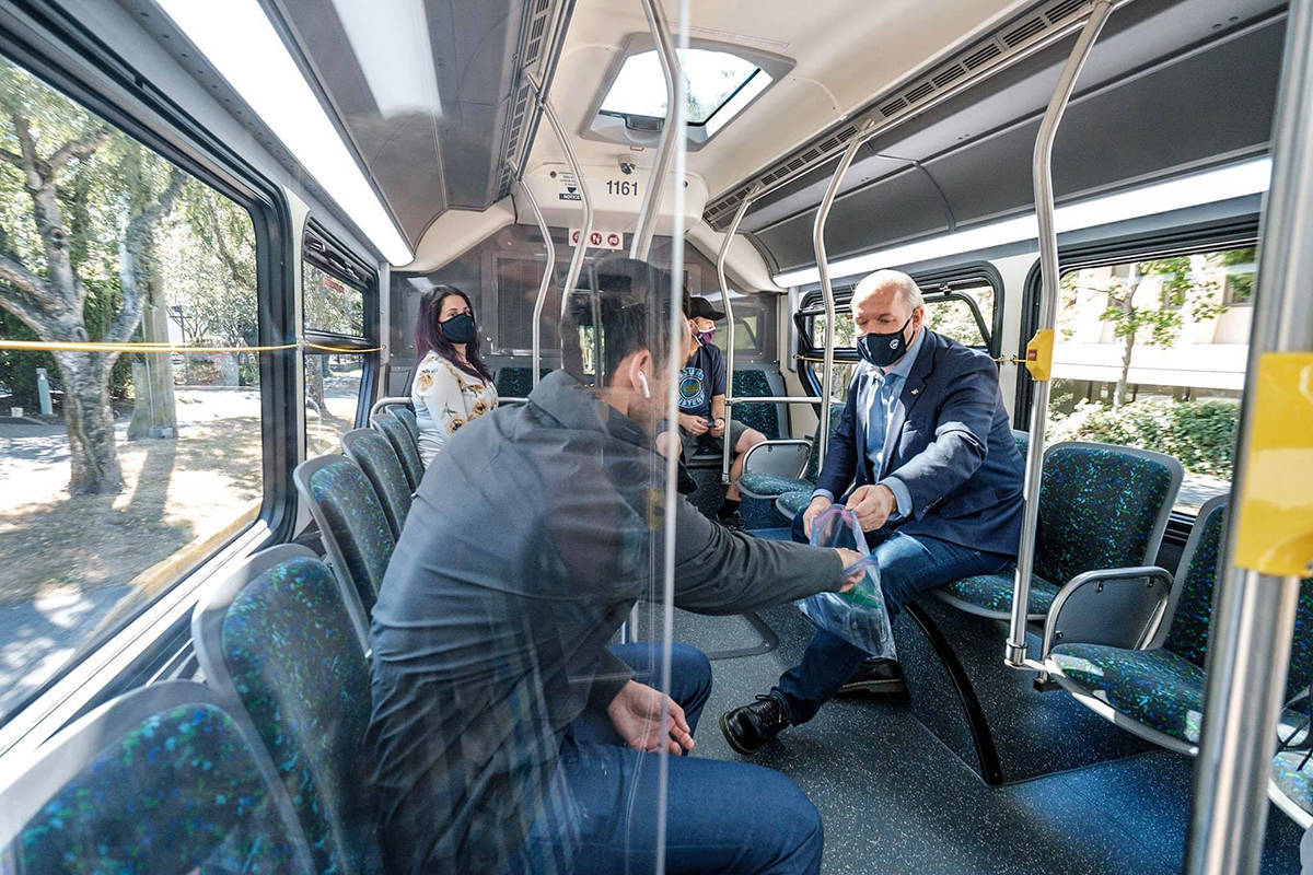 Premier John Horgan took his old bus route around Greater Victoria, handing out masks to BC Transit passengers in July 2020 as masks became required on transit. (John Horgan/Facebook)
