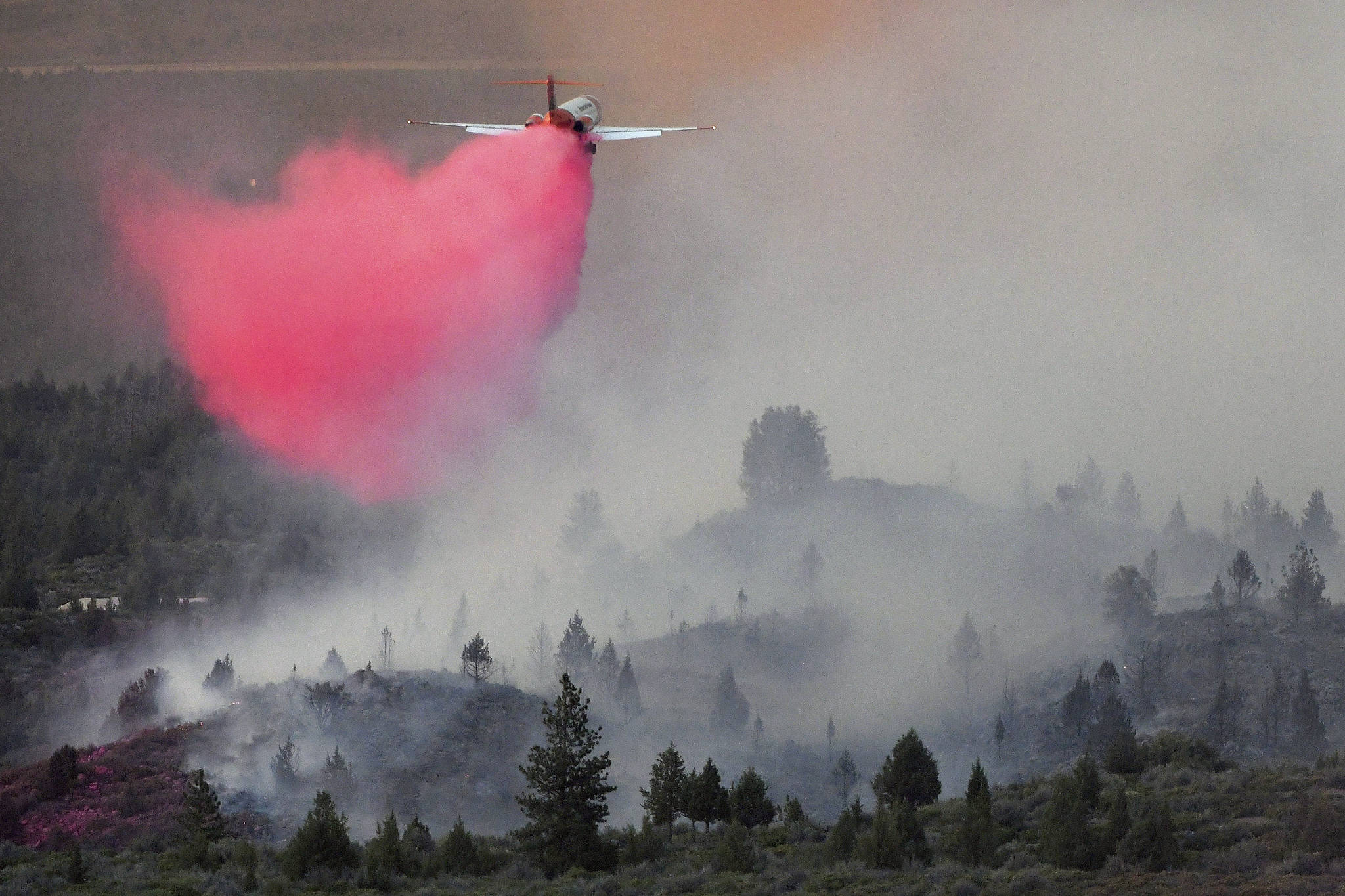 In this Monday, June 28, 2021, photo Tanker 105, an MD-87 aircraft operated by Erickson Aero Tanker of Hillsboro, Ore., drops retardant in an effort to stop the advancing Lava Fire northeast of Weed, Calif. A wildfire that has put thousands of people under evacuation orders in Northern California grew substantially but firefighters had some success against the flames, authorities said Wednesday, June 30. Burning in the shadow of the towering Mount Shasta volcano, the Lava Fire was ignited by lightning last week. (Scott Stoddard/Grants Pass Daily Courier via AP)