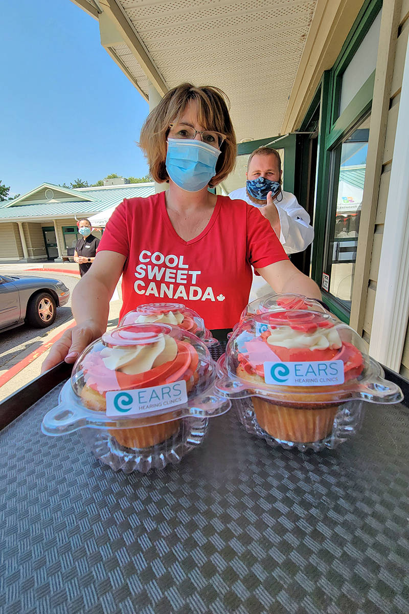 Langley Senior Resources Society centre Reception Services Supervisor Janet Madden showed off some Canada-Day theme cupcakes, while centre sous chef Matt Klar gave a thumbs-up, on Wednesday, June 30. (Dan Ferguson/Langley Advance Times)