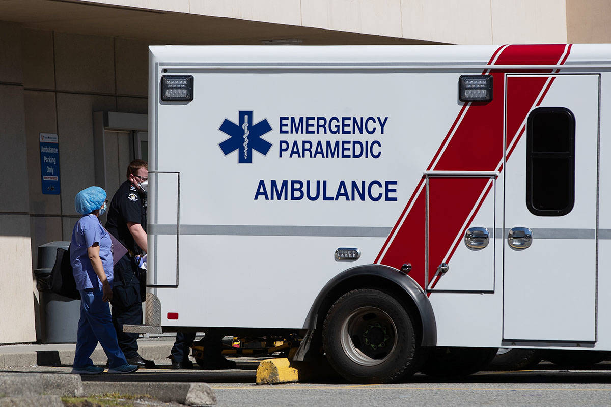 FILE – A healthcare worker watches as a B.C. Ambulance Service paramedic moves a patient into an ambulance outside the emergency department at Royal Columbian Hospital in New Westminster, B.C., on Sunday, April 12, 2020. THE CANADIAN PRESS/Darryl Dyck