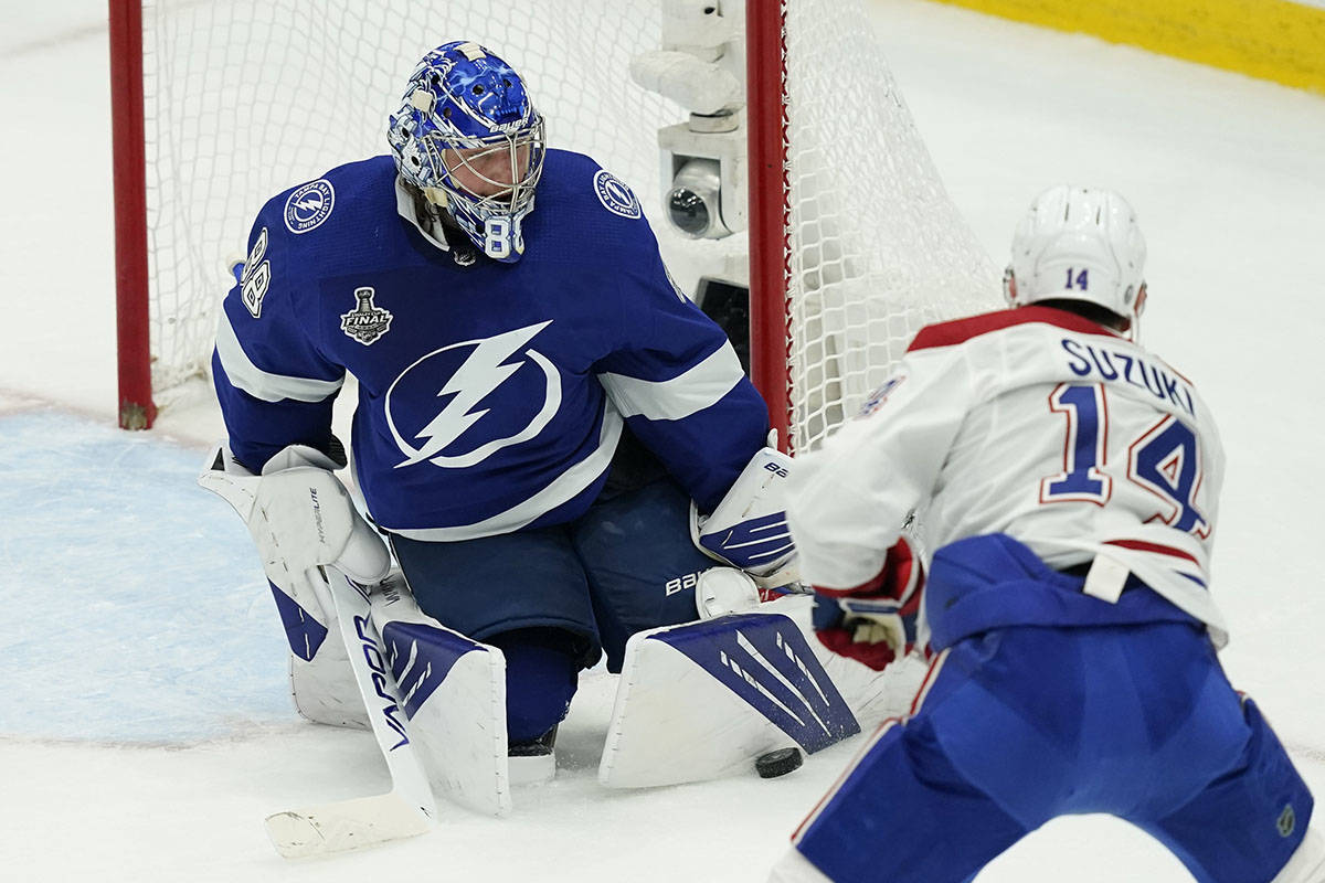 Tampa Bay Lightning goaltender Andrei Vasilevskiy (88) blocks a shot by Montreal Canadiens center Nick Suzuki (14) during the first period in Game 2 of the NHL hockey Stanley Cup finals, Wednesday, June 30, 2021, in Tampa, Fla. (AP Photo/Gerry Broome)