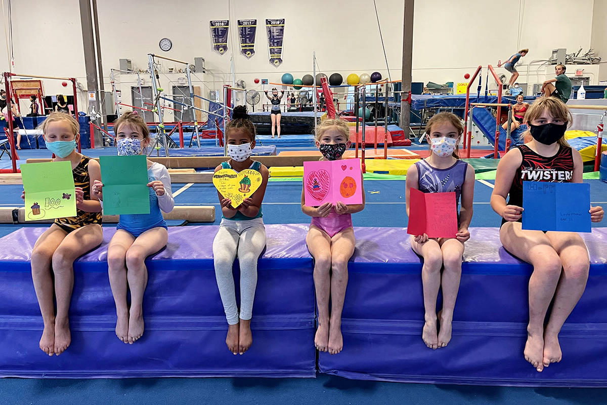 Young Flip City gymnasts show off the cards they created for John Kromhoff's 100th birthday.(Special to Langley Advance Times)