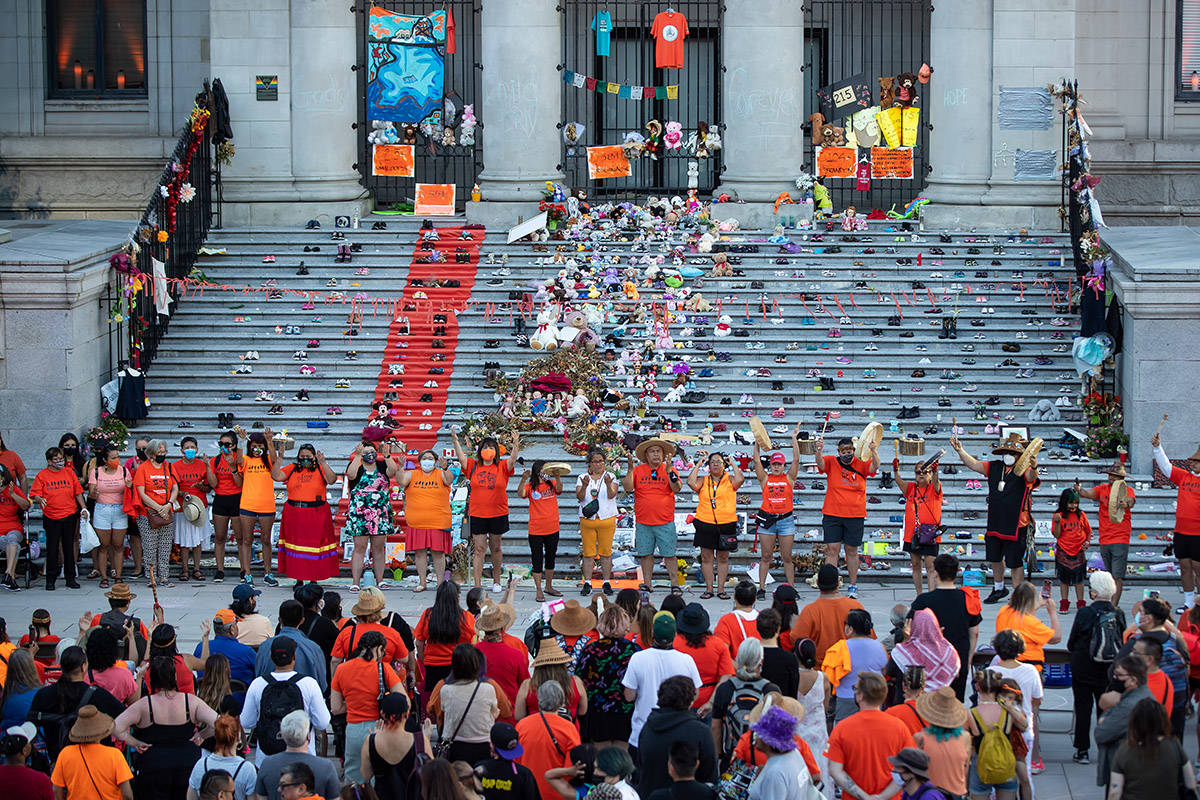 First Nations people raise their hands up after singing and drumming during a ceremony and vigil for the 215 children whose remains were found buried at the former Kamloops Indian Residential School, in Vancouver, B.C., on National Indigenous Peoples Day, Monday, June 21, 2021. THE CANADIAN PRESS/Darryl Dyck