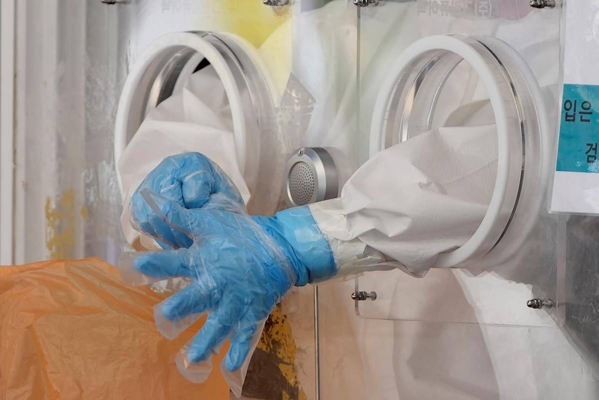 A medical worker wearing protective gear wears plastic gloves in the sweltering heat at a coronavirus testing site in Seoul, South Korea, Friday, July 2, 2021. (AP/Lee Jin-man)