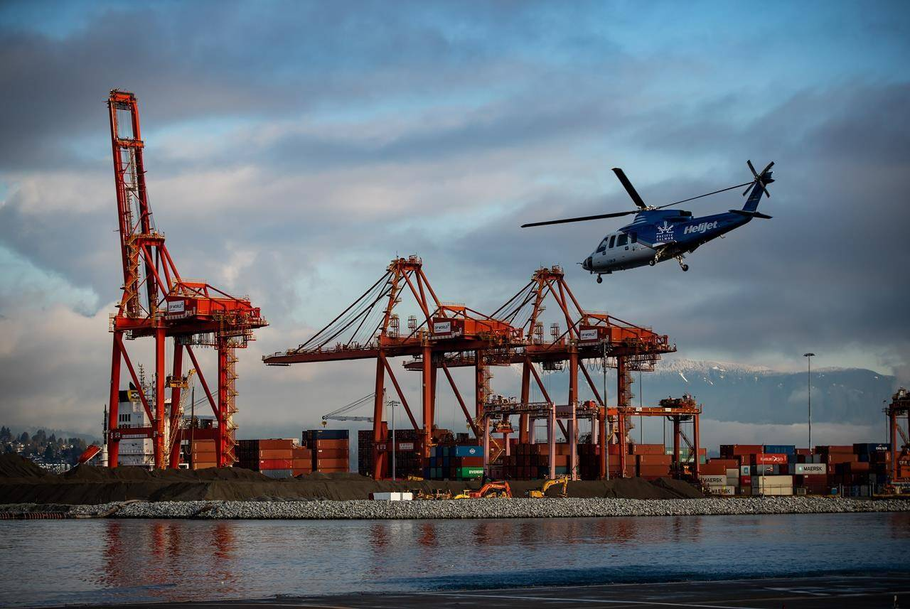 A Helijet passenger helicopter lifts off from a helipad on the harbour past gantry cranes used to load and unload container ships at the DP World terminal at port, in Vancouver, B.C., Monday, Dec. 28, 2020. THE CANADIAN PRESS/Darryl Dyck