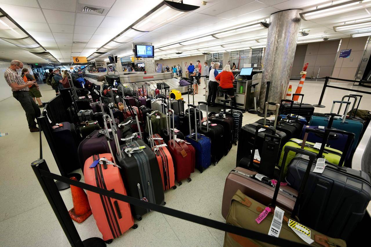 Baggage stacks up from delayed travellers in the baggage claim area in Denver International Airport Wednesday, June 16, 2021, in Denver. The Biden administration is planning to require that airlines refund fees on checked baggage if the bags get seriously delayed. (AP/David Zalubowski)