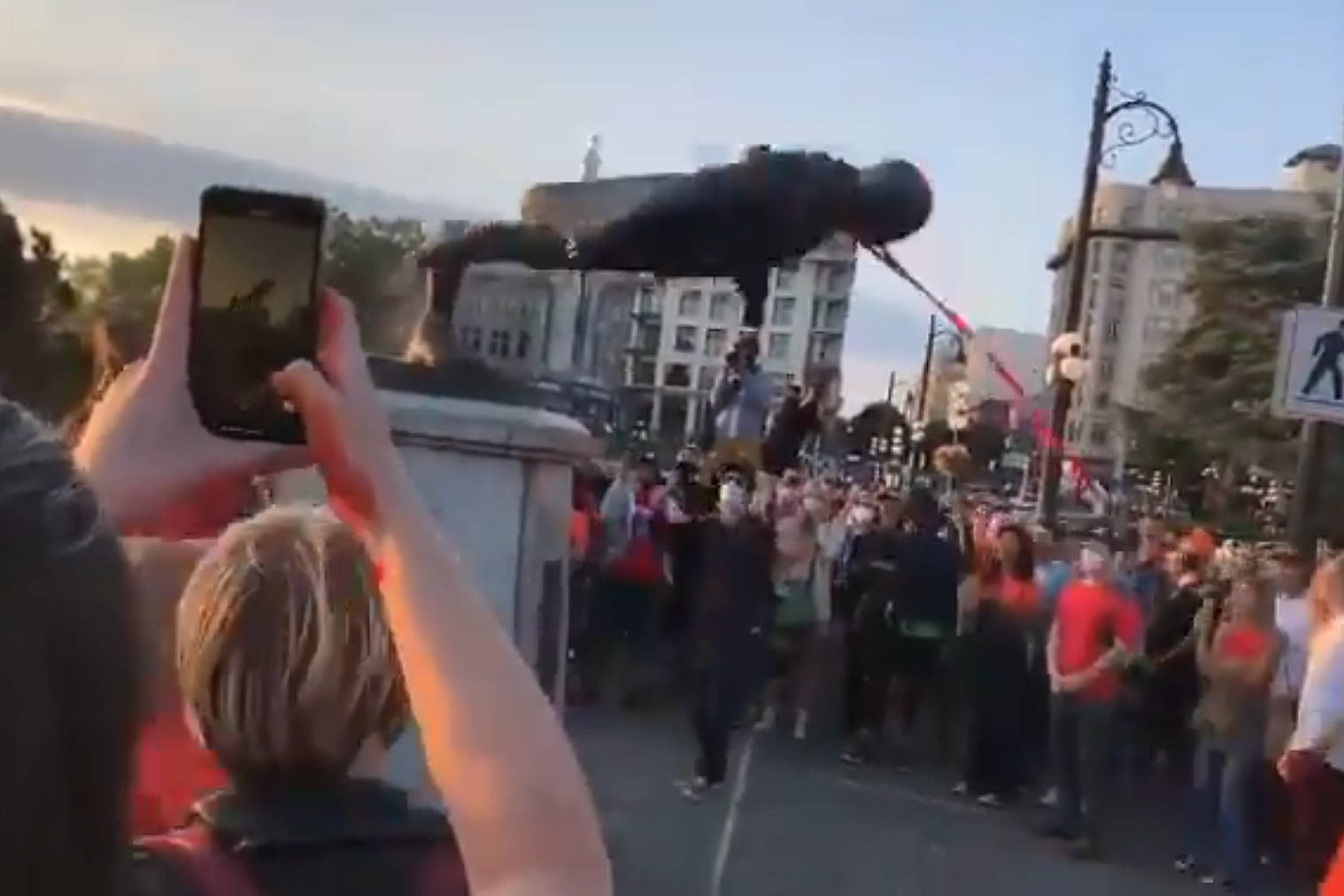 A crowd pulls down the Captain James Cook statue in downtown Victoria. (Siiam Hamilton/Twitter)