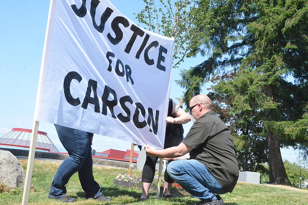 Aron Crimeni, right, with family and friends set up a Justice For Carson banner on Friday, July 2. It's been almost two years since the Langley teen died and the family wants to see charges laid. (Matthew Claxton/Langley Advance Times)