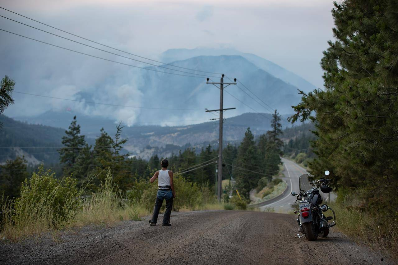 Alfred Higginbottom, of the Skuppah Indian Band, a Nlaka'pamux First Nations government, watches as a wildfire burns on the side of a mountain in Lytton, B.C., Thursday, July 1, 2021. THE CANADIAN PRESS/Darryl Dyck
