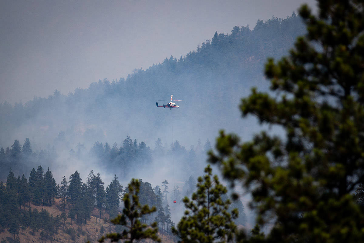 A helicopter pilot prepares to drop water on a wildfire burning in Lytton, B.C., on Friday, July 2, 2021. THE CANADIAN PRESS/Darryl Dyck