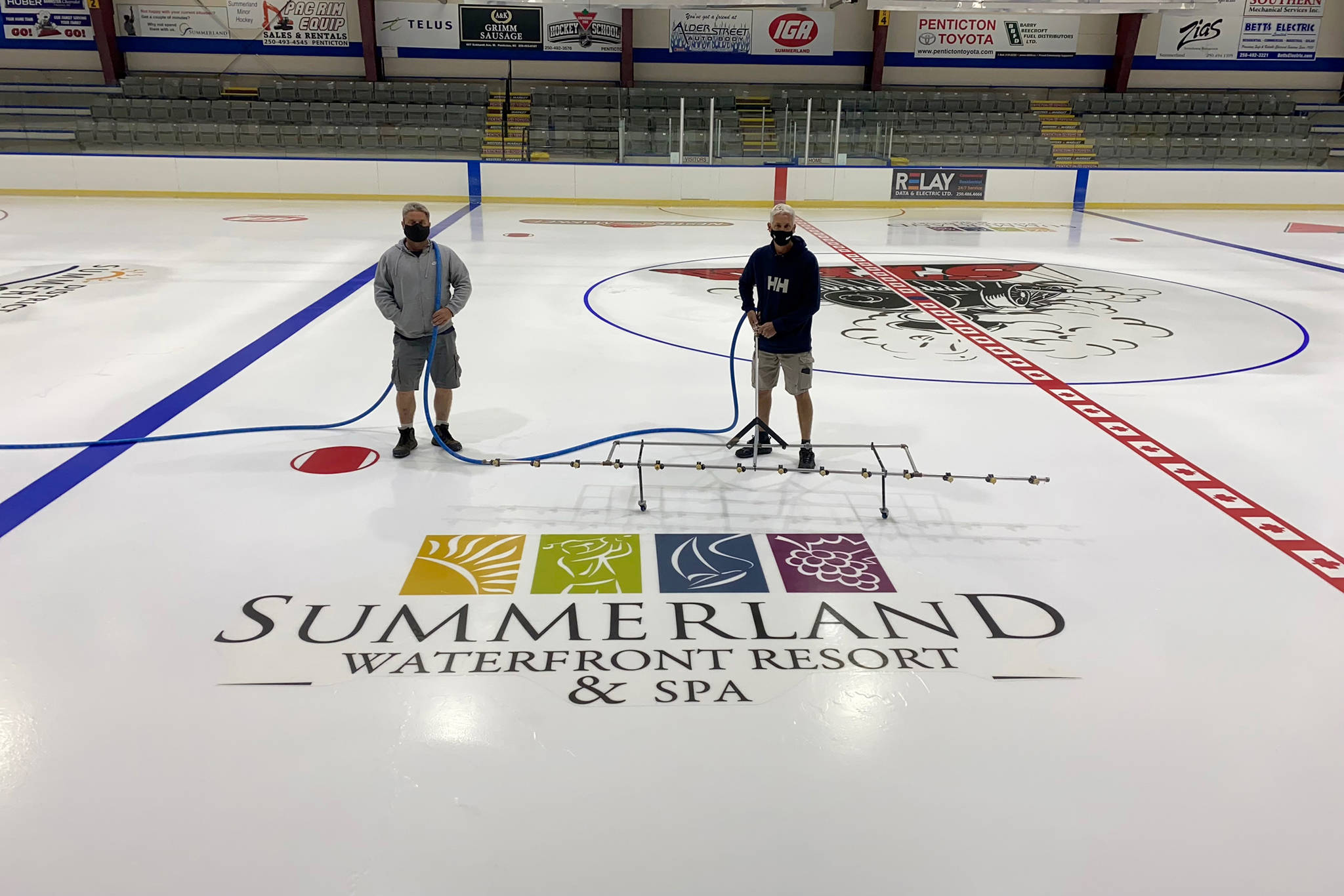 Erik Laflamme, left, and Mike Fetterer work on the ice at the Summerland Arena. The process of putting in the ice and getting it ready for summer use takes around one week. The summer ice will be ready by July 5. (John Arendt - Summerland Review)
