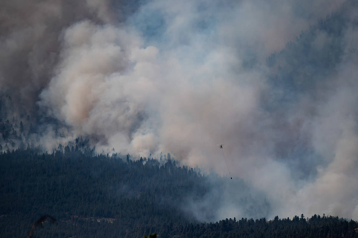 A helicopter pilot prepares to drop water on a wildfire burning in Lytton, B.C., on Thursday, July 1, 2021. THE CANADIAN PRESS/Darryl Dyck