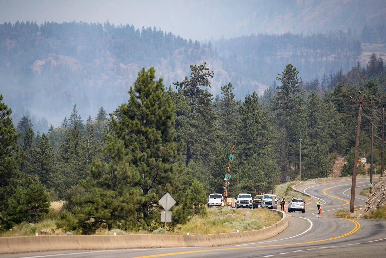 RCMP officers man a roadblock on the Trans-Canada Highway as wildfire burns in Lytton, B.C., Friday, July 2, 2021. The BC Wildfire Service says there has been minimal growth in fire that destroyed much of the village of Lytton, B.C., in the past day .THE CANADIAN PRESS/Darryl Dyck