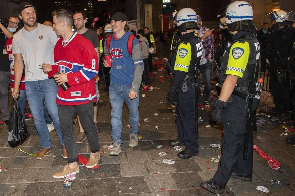Police officers keep an eye on Montreal Canadiens fans following game 3 of the NHL Stanley Cup final between the Canadiens and the Tampa Bay Lightning outside the Bell Centre in Montreal, Friday, July 2, 2021. THE CANADIAN PRESS/Graham Hughes